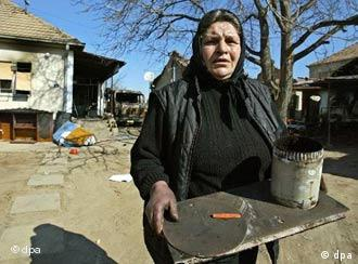 An ethnic Serb woman carries some of her belongings as she and her family prepare to leave their home in Kosovo Polje