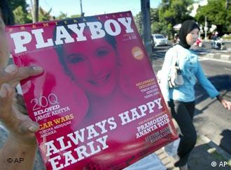 A vendor shows Indonesian version of Playboy magazine to passing motorists as a Muslim woman walks past by on a street in Jakarta, Friday, April 7, 2006. The toned-down edition of Playboy went on sale Friday in the world's most populous Muslim nation, defying demands from Islamic leaders that the publication be banned. (AP Photo/Irwin Fedriansyah)