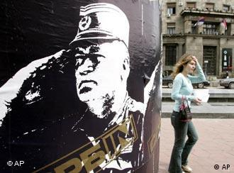 A pedestrian walking by a poster of war crimes fugitive Bosnian Serb commander Ratko Mladic on a main square in the Serbian capital, Belgrade