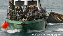 Ein Boot der spanischen Küstenwache bringt afrikanische Füchtlinge nach Fuerteventura; die Küstenwache hatte sie auf einem heruntergekommenen Boot, dessen Wrack (l) sie im Schlepp hat, auf dem Meer vor den Kanarischen Inseln abgefangen (Archivfoto vom 19.10.2004). Viele der Migranten sind eigentlich wohlhabende Menschen, eine Reise nach Europa kann bis zu 10.000 Dollar kosten. Doch die Chancen, den gelobten Kontinent zu erreichen, werden immer geringer. Von Afrika aus führen viele Routen nach Europa, Ceuta und Melilla sind nur eine der möglichen Zwischenstationen. Foto: Juan Medina (zu dpa 0617) +++(c) dpa - Bildfunk+++ Afrika, Gesellschaft, Migration, Politik