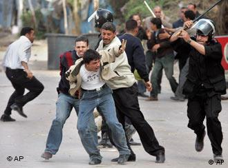 An Egyptian Coptic protester, center, is beaten as he is taken away by plain-clothes and uniformed policemen outside the St. Maximus Church in the northern Mediterranean city of Alexandria, Egypt Sunday, April 16, 2006. Police fired live ammunition into the air and lobbed tear gas into rioting crowds of Christians and Muslims Sunday in a third day of sectarian violence in Egypt's second-largest city. (AP Photo/Ben Curtis)