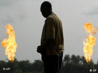 An unidentified man stands near a gas flare belonging to the Agip Oil company in Idu Ogba, Niger Delta area