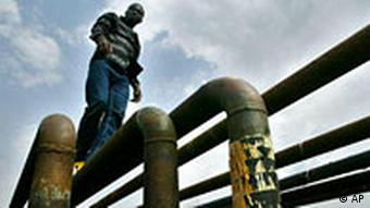 Man standing on top of an oil pipeline