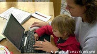 A woman with a child on her lap working at a laptop