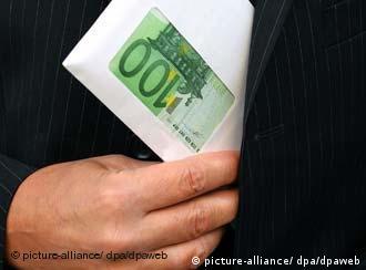 Eine Hand fasst einen Umschlag Hundert-Euro-Scheinen