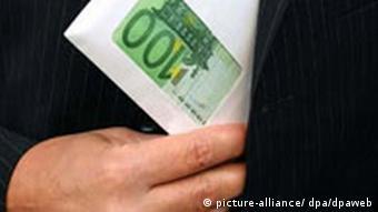Ein Mann steckt einen Umschlag mit Geldscheinen ein, Foto: dpa