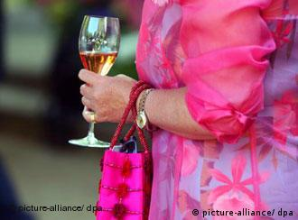 A woman in a bright pink dress holding a glass of champagne