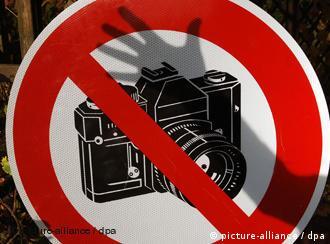 Der Schatten einer Hand ist auf einem Fotografier-Verbotsschild zu sehen (Foto: dpa)