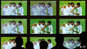 People watch a wall of televisions showing a soccer game
