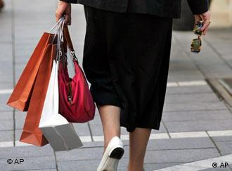 A woman carries shopping bags and sunglasses