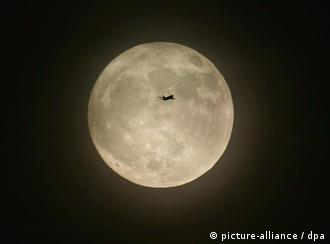 An aircraft passing the almost full moon
