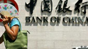 Frau mit Fächer vor dem Schriftzug Bank of China. Quelle: AP.