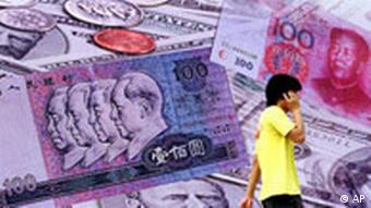 A man walks past a photograph of yuan banknotes