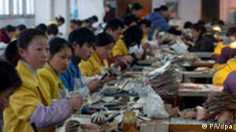 Workers make leather shoes at a shoe factory in Yancheng in east China's Jiangsu province