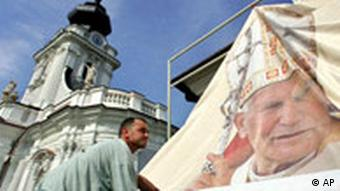 A worker adjusts a poster showing a late pope John Paul II in his hometown of Wadowice near Krakow