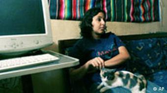 Una joven de 23 años, Manal Hassan, se encuentra sentada sobre un sofá, al lado de un ordenador. Sobre ella se sienta su gata.