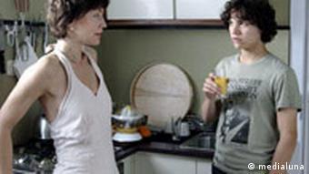 Mutter und Junge stehen in der Küche und unterhalten sich mit ernstem Blick miteinander