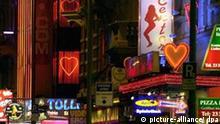 Bunt leuchten die Neonreklameschilder in der Taunusstraße im Rotlichtviertel von Frankfurt am Main (Archivfoto vom 12.11.2003). Gegenüber des Hauptbahnhofs und im Schatten der Bankentürme befindet sich das Frankfurter Bahnhofsviertel - in dem auch der Rotlichtbezirk liegt -, das wie kaum eine andere Gegend in Deutschland für Sex, Drogen und Kriminalität steht. Rechtzeitig zur Fußball-WM 2006 soll das Viertel schöner und lebenswerter werden. Zehn Millionen Euro stellt die Stadtverwaltung dafür zur Verfügung. Foto: Arne Dedert (zu dpa-Reportage: Das Frankfurter Bahnhofsviertel soll wieder lebenswert werden vom 06.10.2005) +++(c) dpa - Report+++