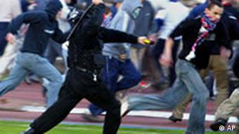 A Polish police man battles with fans after rival fans stormed the field to fight each other after a soccer match between Gornik Zabrze and Legia Warsaw in Zabrze, Poland, on Wednesday, May 10, 2006. Police in riot gear used rubber bullets and a water cannon to disperse the hooligans. Seven people were arrested, and two police officers were injured in the melee. ( AP Photo/Irek Dorozanski)