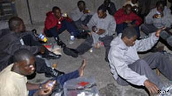 Would-be immigrants rest after arriving in Europe aboard a wooden fishing boat