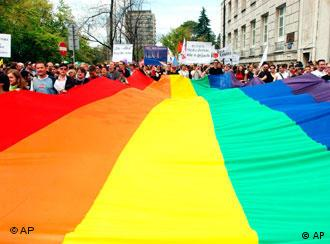 A giant multicolor flag is carried by marchers during a gay rights parade