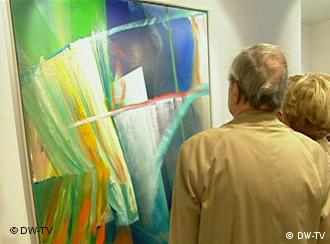 A couple looks at a piece of modern art at an exhibition
