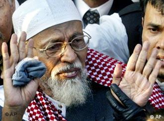 Muslim cleric Abu Bakar Bashir waves to supporters surrounding him
