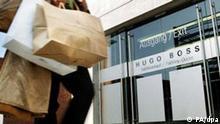 Eine Frau mit Einkaufstüten läuft am Dienstag (25.03.2003) in Metzingen am Ausgang des Hugo Boss-Fabrikverkaufs in Metzingen vorbei. Fast 50 so genannte Factory Outlet Center locken die Kunden mit Rabatten in die schwäbische Kleinstadt. Foto: Marijan Murat dpa/lsw (zu lsw-Korr: Smart Shopper-Paradies: Auch Japaner machen Schnäppchen in Metzingen)