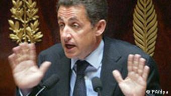 French President Nicolas Sarkozy sits in front of a brown and gold background