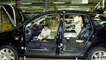 Employees build a car in a VW factory