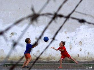 Two children play with a ball behind barbed wire