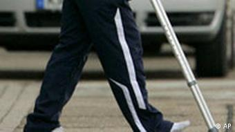Footballer Michael Owen walks with crutches