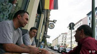 German Turks in front of a cafe with a German flag behind them