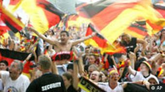 German soccer fans party at the public viewing area in Berlin, waving German flags