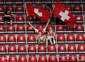 Two Swiss fans in a nearly empty block of seats at a World Cup match in 2006