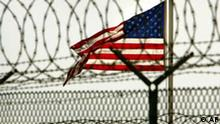 In this photo, reviewed by a US Department of Defense official, an American flag waves in the breeze behind razor-wire and fences within the compound of Camp Delta military-run prison, at the Guantanamo Bay U.S. Naval Base, Cuba on Tuesday, June 27, 2006. The Supreme Court ruled Thursday that President George W. Bush overstepped his authority in creating military war crimes trials for Guantanamo Bay detainees, a rebuke to the administration and its aggressive anti-terror policies. (AP Photo/Brennan Linsley)