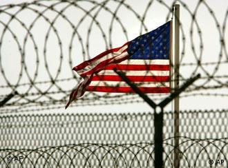 Eine amerikanische Flagge hinter einem Stacheldrahtzaun im Camp Delta