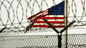 An American flag waves in the breeze behind razor-wire and fences