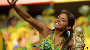 A supporter of Brazil's soccer team cheers with a replica of the World Cup trophy in Germany last year