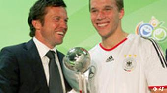 Former German soccer star Lothar Matthaeus, left, hands over to German player Lukas Podolski, right, the FIFA best young player trophy in Berlin, Friday, July 7, 2006. Podolski received the award as best young player of the Soccer World Cup tournament 2006 in Germany.