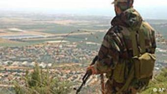 Armed Lebanese Hezbollah militant looks towards northern Israel on the Lebanese-Israeli border