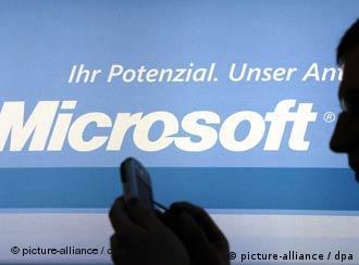 Vor dem Logo von Microsoft macht sich ein Mitarbeiter am CeBit-Stand in Hannover auf einem Taschen-PC Notizen (Archivfoto vom 24.03.2004).