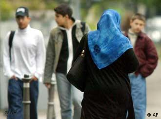 A woman with a headscarf on walking toward a group of people