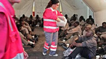 Red Cross workers in red safety jackets handing out biscuits to African migrants