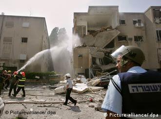 Equipos de salvamento israelíes intentan apagar un incendio en Haifa, provocado por un cohete de Hizbolá.