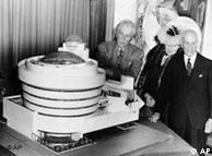 فرانک لوید رایت (چپ) در کنار ماکت ساختمان موزهی گوگنهایم، به همراه سولومون گوگنهایم (راست)،سفارشدهندهی طرح موزه، و  هنرمند آلمانی هیلا فون ریبی که در طراحی و تحقق ساختمان موزهی گوگنهایم تاثیری بهسزا داشته است