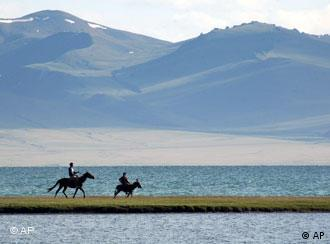 Two people ride a horse and a donkey along a narrow strip of land on Lake Son-Kul with the Tien Shan mountains in the background.