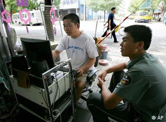 A shop owner man uses the Internet at the entrance to his shop, as a security guard looks on in Beijing Thursday July 20, 2006. The man offers Internet access, online chatting and downloads of movies and music for customers at his one-computer Internet bar. Amnesty International accused Yahoo, Microsoft and Google on Thursday of violating human rights principles by cooperating with China's efforts to censor the Web and called on them to lobby for the release of jailed cyber-dissidents. (AP Photo/Greg Baker)