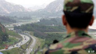 A South Korean soldier looks at South Korean vehicles crossing the border line from Diamond Mountain in North Korea