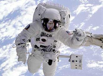 Ein Astronaut im Weltraum – im Hintergrund weiße Wolken und hellblaues Wasser der Erde